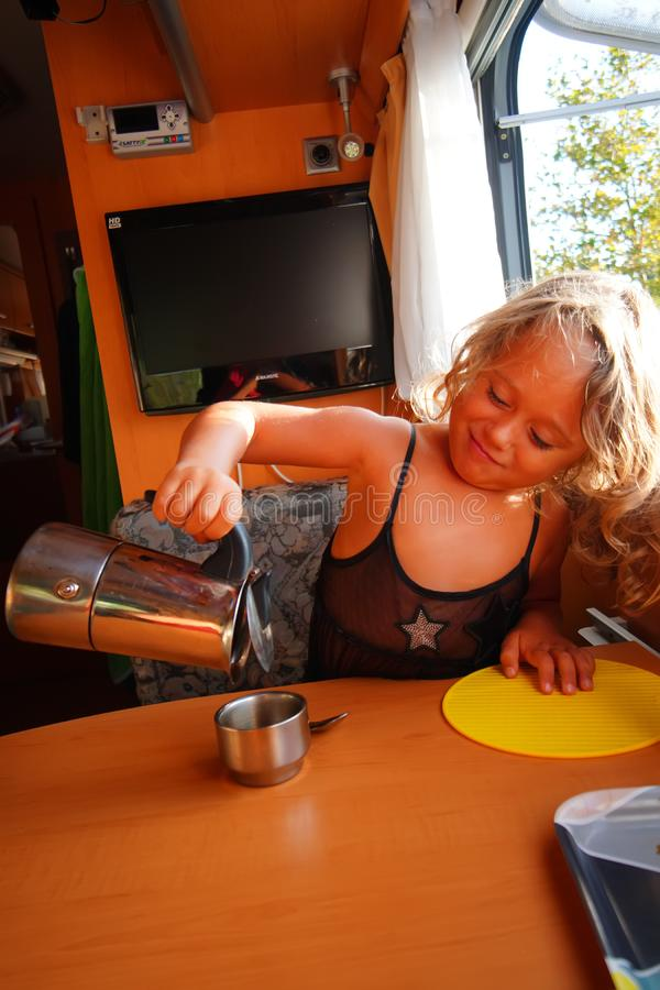 4-5 year old girl drinking coffee in her motorhome during her holidays. In Greece, people, play, action, dock, little, kids, mountain, young, active, adventure stock photography