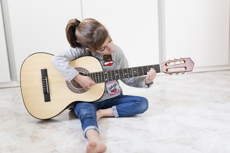 9 year old girl learning to play the guitar. stock photo