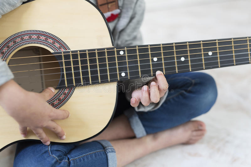 9 year old girl learning to play the guitar. stock photography