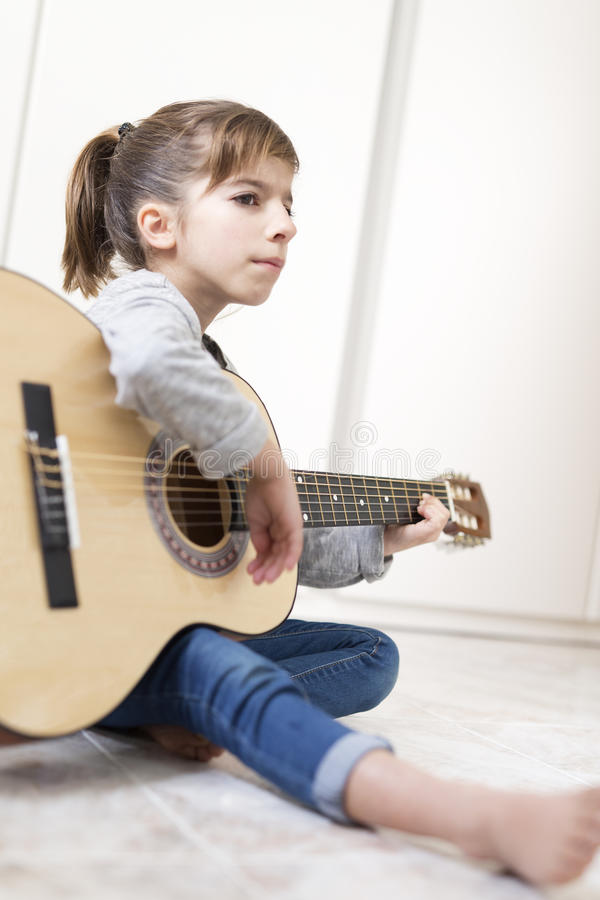 9 year old girl learning to play the guitar. royalty free stock photos