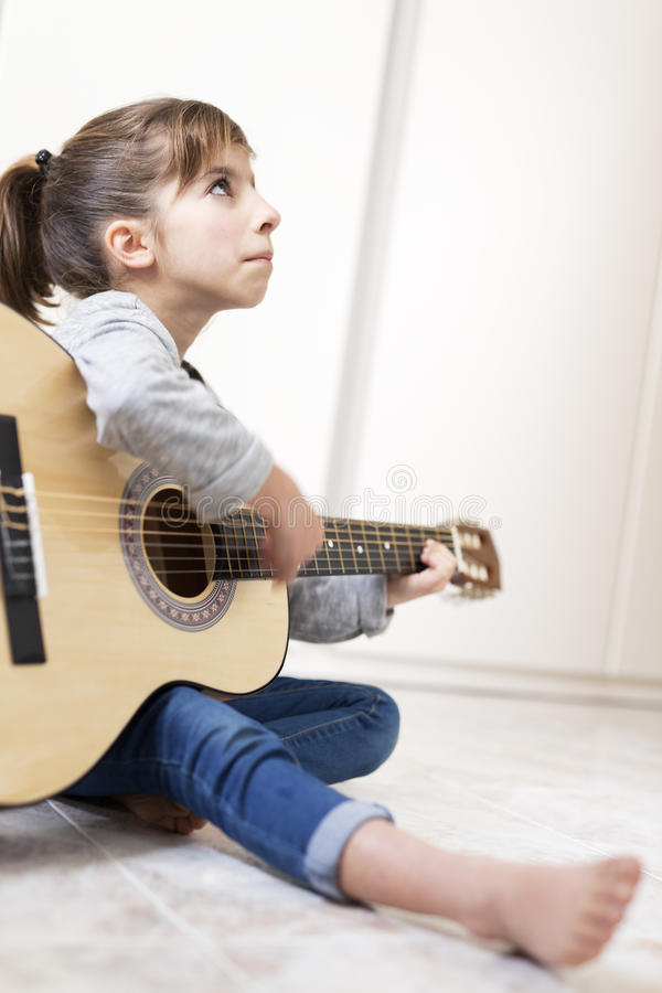 9 year old girl learning to play the guitar. stock images