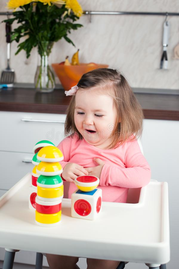 A 2 year old girl with long hair plays with a designer construction at home, builds towers, rejoices at successes, vertical photo.  stock photography