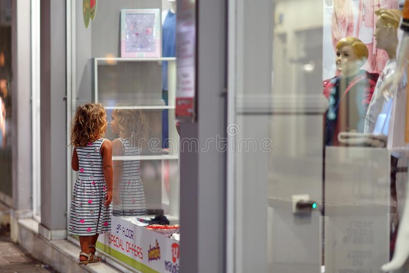 A 3-4 year old girl looks at a shop window in Chania stock image
