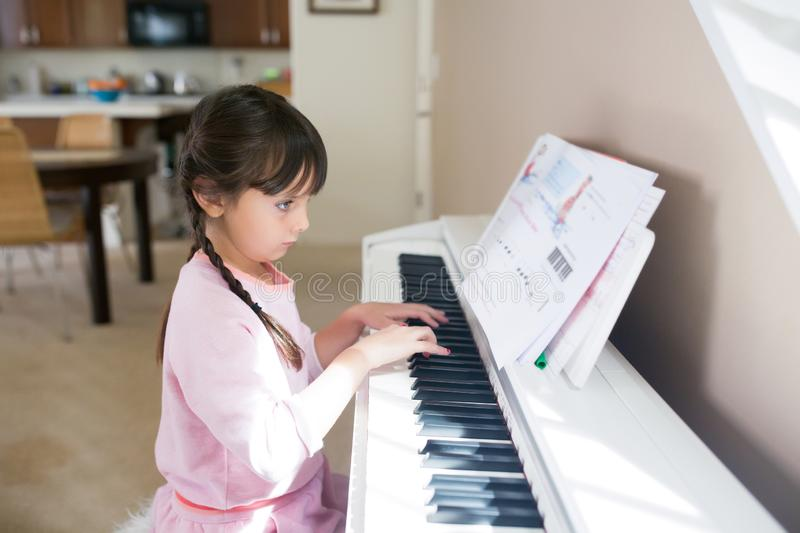 Girl playing piano and reading musical notes royalty free stock image