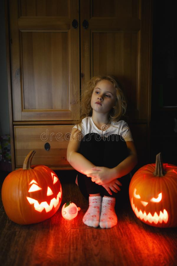 6 year old girl sitting on the floor with two scary halloween pumpkins at night. 6 year old girl sitting on the floor with two scary halloween pumpkins at night stock image