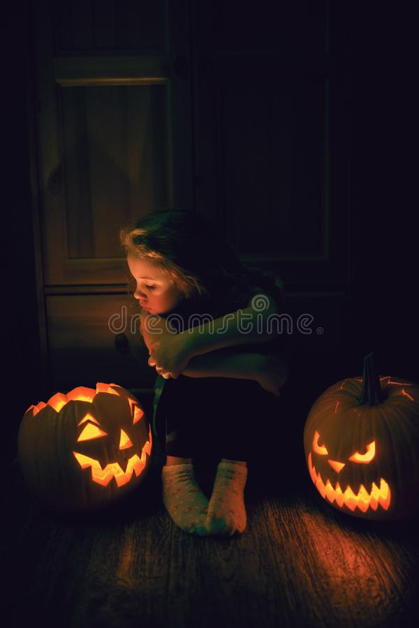 6 year old girl sitting on the floor with two scary halloween pumpkins at night. 6 year old girl sitting on the floor with two scary halloween pumpkins at night royalty free stock photography