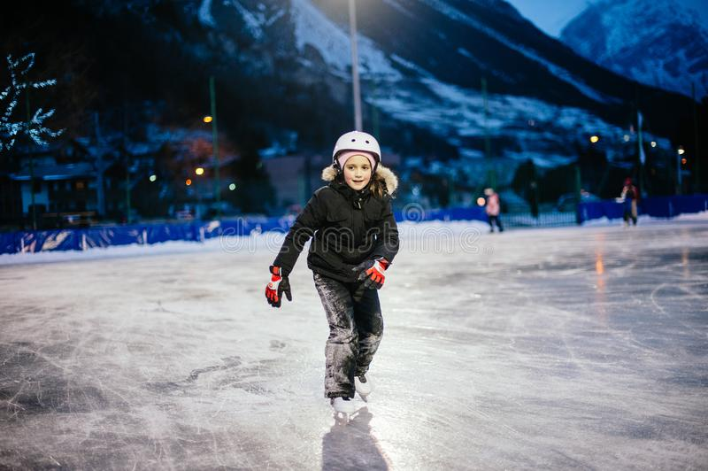 9 year old girl skates on the ice in the evening on an illuminated track stock photos