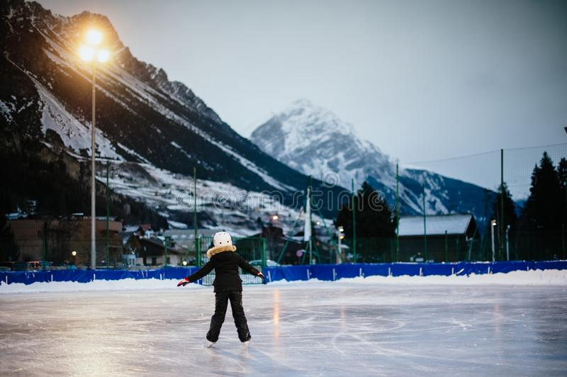 9 year old girl skates on the ice in the evening on an illuminated track royalty free stock photography