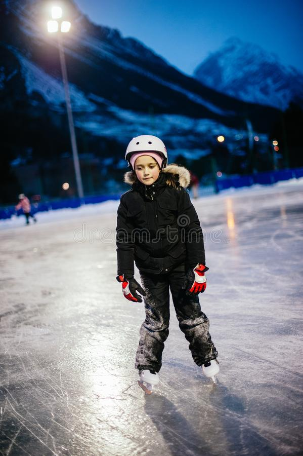 9 year old girl skates on the ice in the evening on an illuminated track royalty free stock images