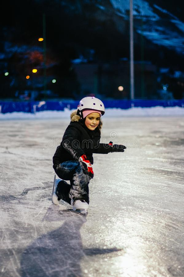9 year old girl skates on the ice in the evening on an illuminated track royalty free stock image