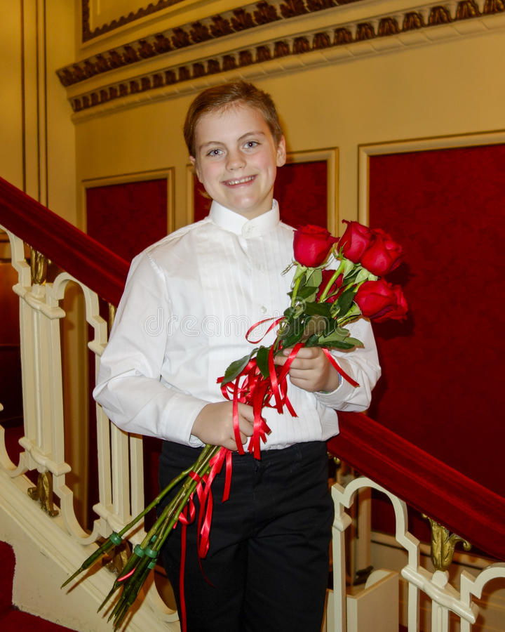 10 year old girl standing on red stairway holding red roses stock image