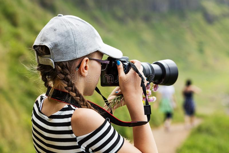 12 year old girl taking pictures in a beautiful scenic of Irish cliffs. 12 year old girl taking pictures with a long lens in a beautiful scenic of Irish cliffs stock images