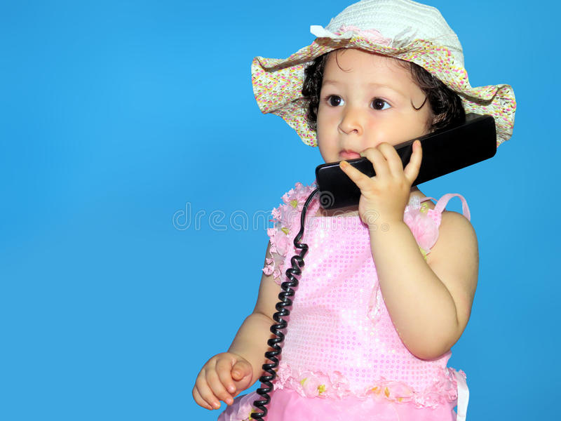 Two year old girl talking on the telephone royalty free stock images