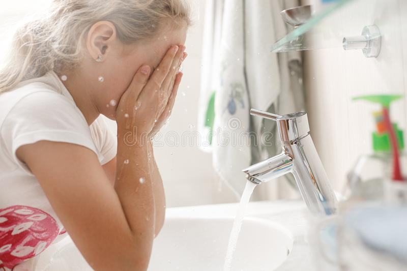 8 year old girl washes her face in the bathroom in the morning royalty free stock photo