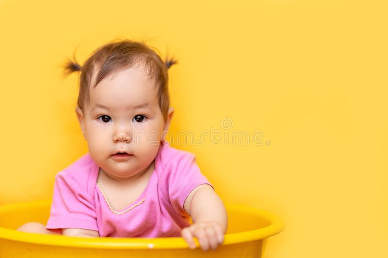 1 year old playful asian caucasian girl mixed race kazakh and german girl on yellow background.  royalty free stock photography