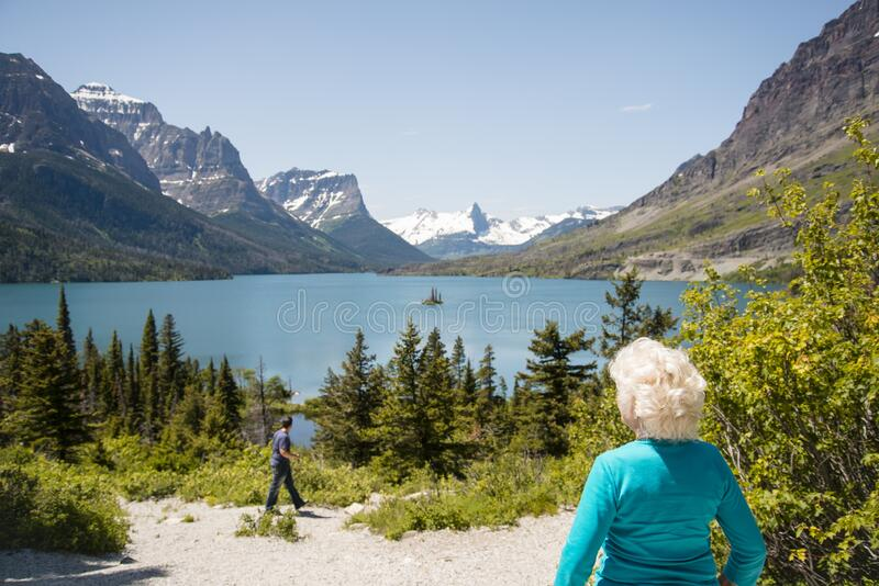 70 year old senior tourist woman looking at mountains and lake scenic view. Enjoying the beauty of nature at Glacier National Park royalty free stock photos