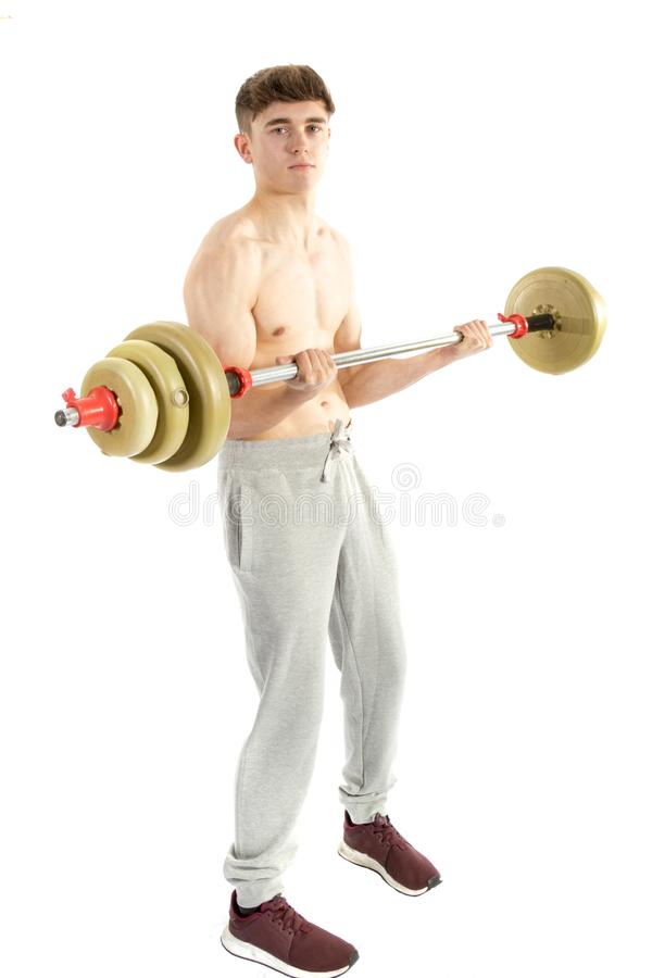 18 Year old teenage boy lifting weights. 18 year old teenage boy using a barbell stock images