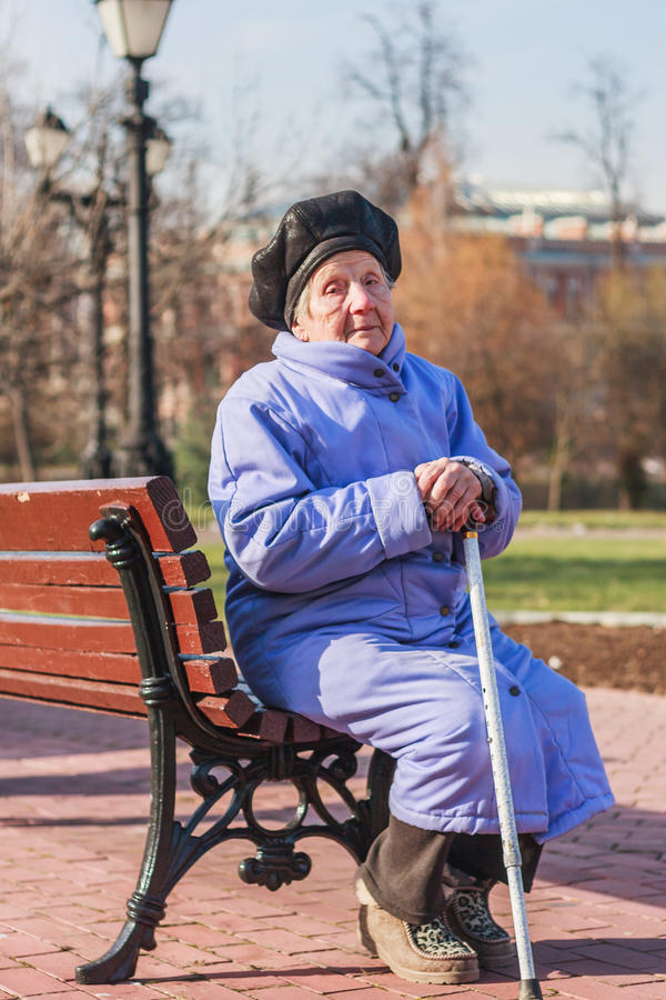89 year old woman sitting on bench. Vertical photo, photo took in Moscow, Russian stock photo