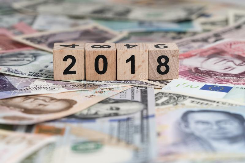 Year 2018 world economic or financial concept with cube wooden b. Lock number 2018 on pile of international mojor countries banknotes royalty free stock images