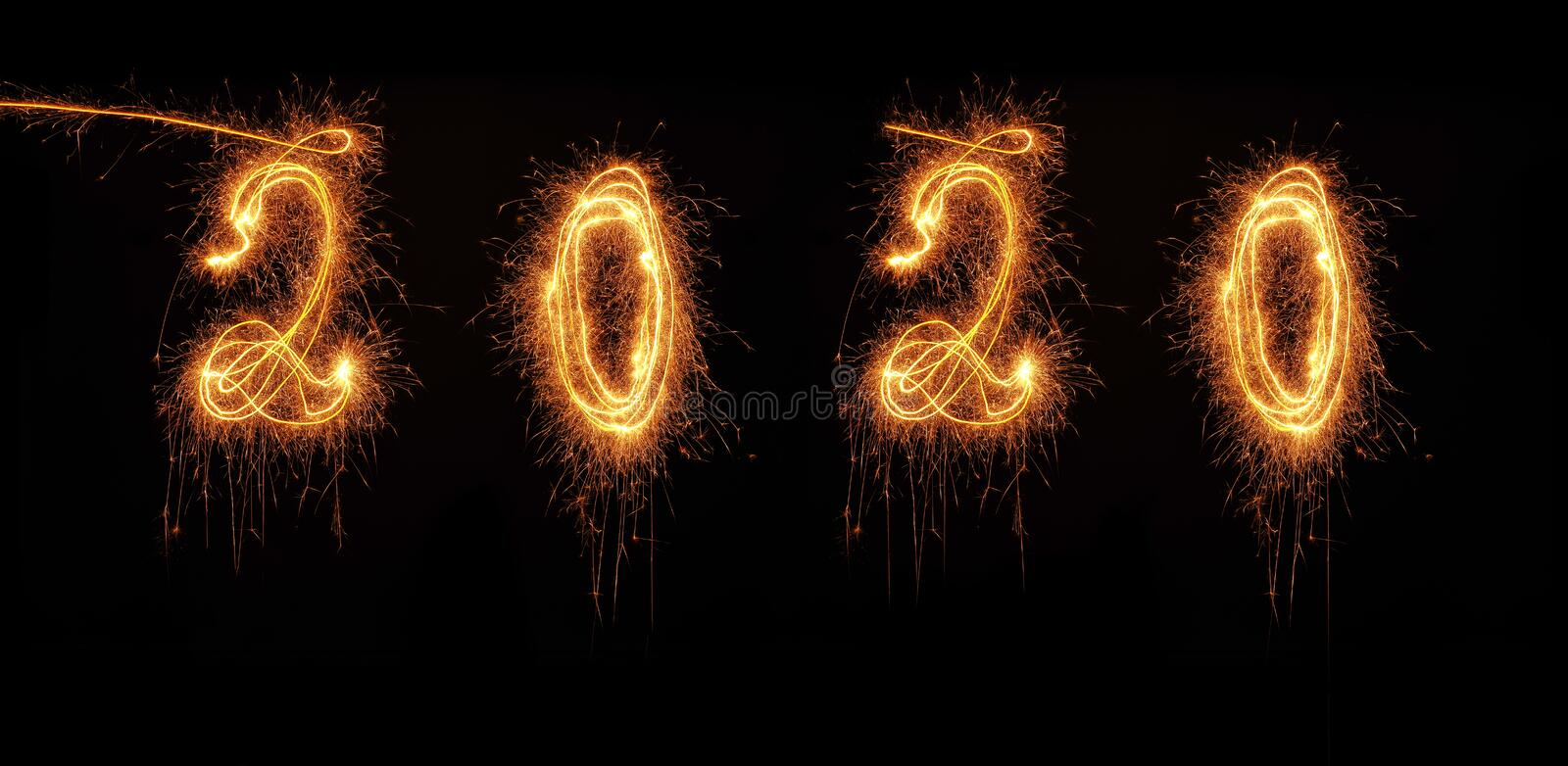 The year 2020 written with a sparkler on black background. New Years concept image stock photography