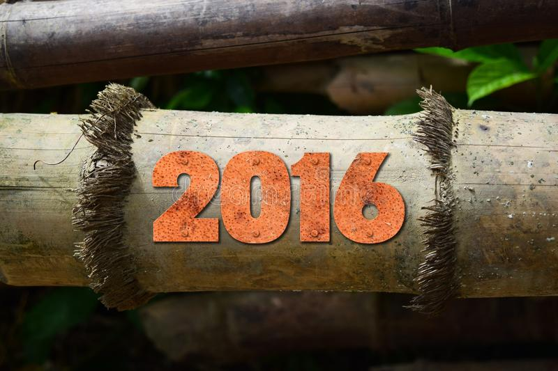 Year 2016 written with vintage letterpress printing blocks on rustic wood background stock photography