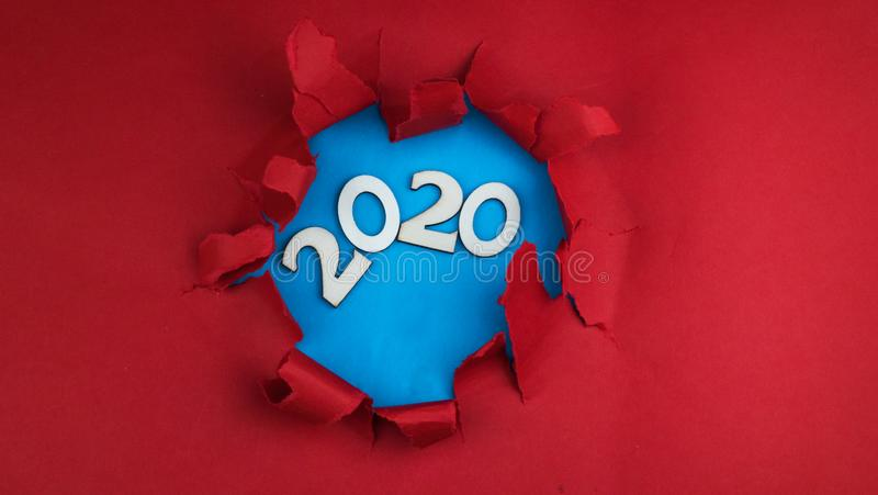 Year 2020 written in wooden numbers or letters on a blue background. in the hole from the red background stock photography