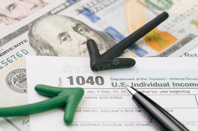 Yearly tax submission concept, arrow pointing with pen on 1040 US individual income tax filling form on pile of US dollar. Banknotes money stock image