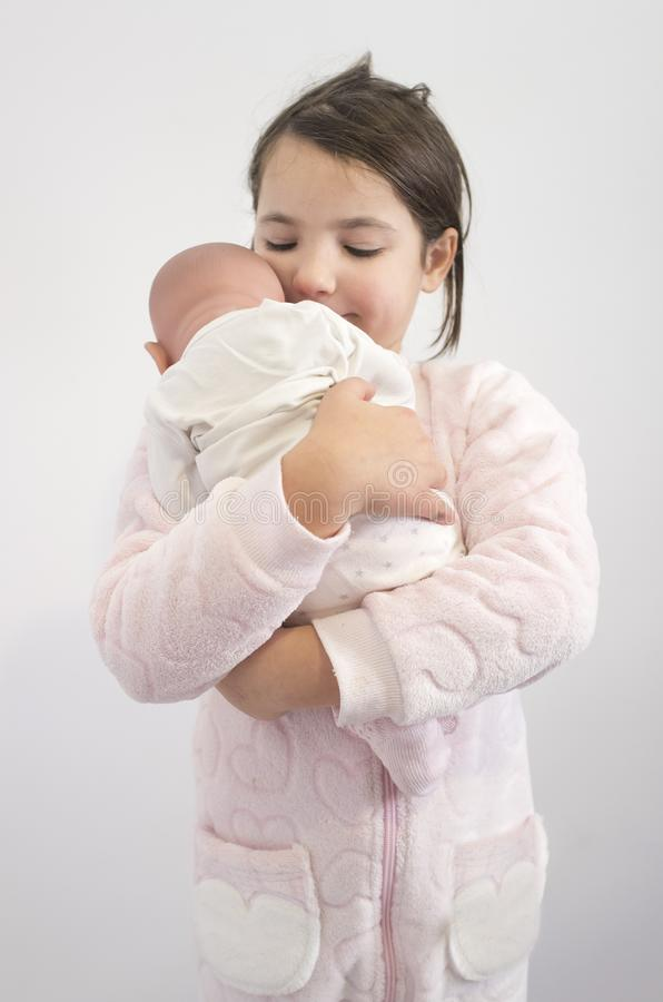 6 years little girl holding affectionately her reborn doll. Over white royalty free stock images