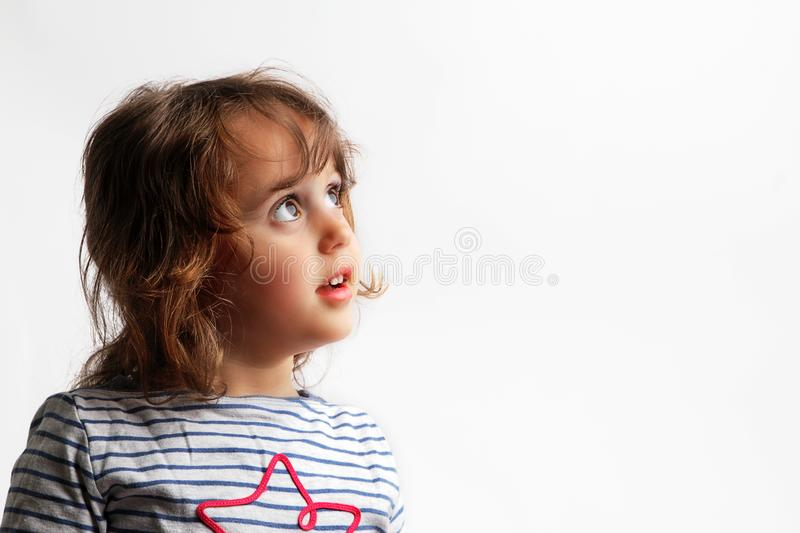 3-4 years little girl looking up. On white background childhood joy expression show lovely female isolated fun adorable kid youth eyes natural cute positive royalty free stock image