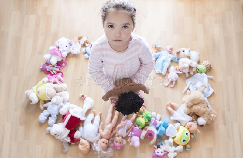 5 years little girl unhappy with lots of toys. Too many toys concept at Infant Behaviour. And Development. Overhead view stock images