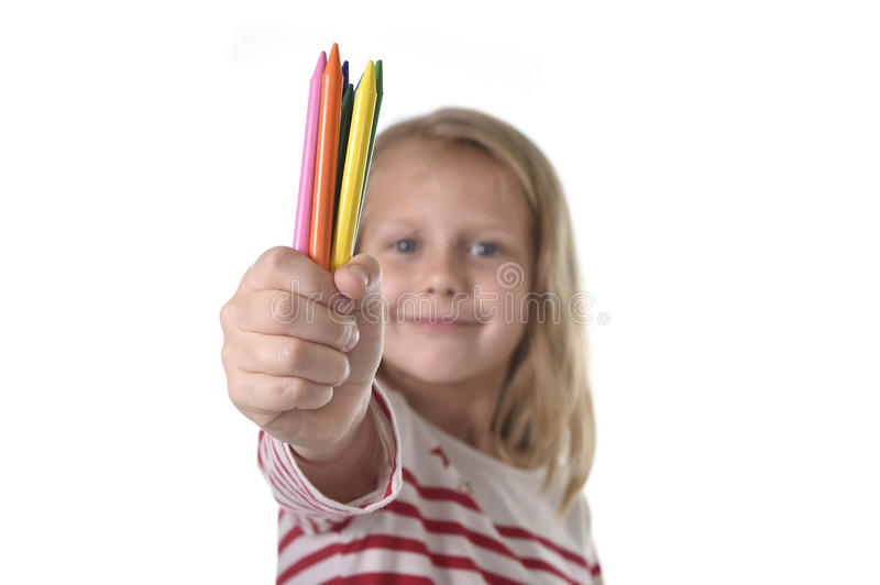 6 or 7 years old beautiful little girl holding multicolor crayons set in art school children education concept. Isolated on white background royalty free stock photos