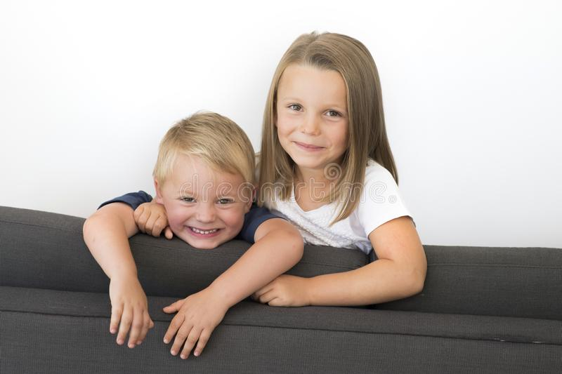 7 years old beautiful little girl posing happy at home sofa couch with her small cute young 3 years old brother in siblings love r. 7 years old beautiful little royalty free stock photo