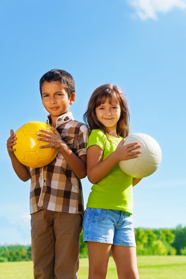 6 years old, boy and girl with balls. Couple of kids 6 years old, boy and girl holding balls in the park stock photography