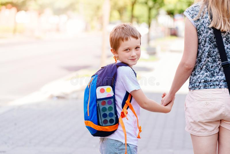 7 years old boy going to school with his mother stock photos