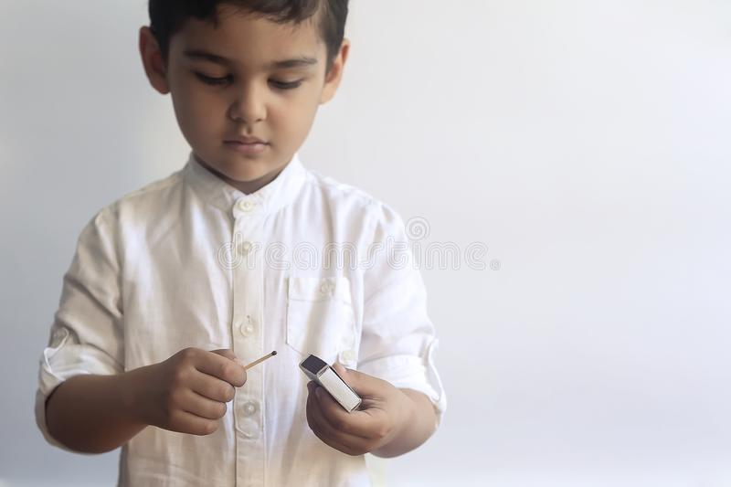 5-6 years old boy playing with fire. Middle eastern kid exploring fire. First tries of a child to play with match sticks. Copy space royalty free stock photography