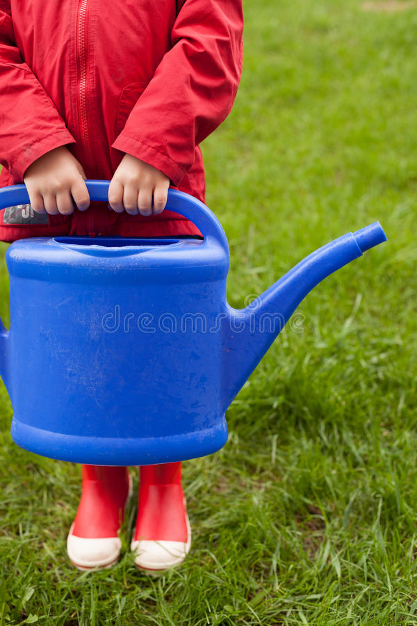Download 4 Years Old Boy In A Red Jacket And Rubber Boots Is Going To Water A Tree And From A Nice Big Blue Watering Can. Stock Photo - Image: 73086390