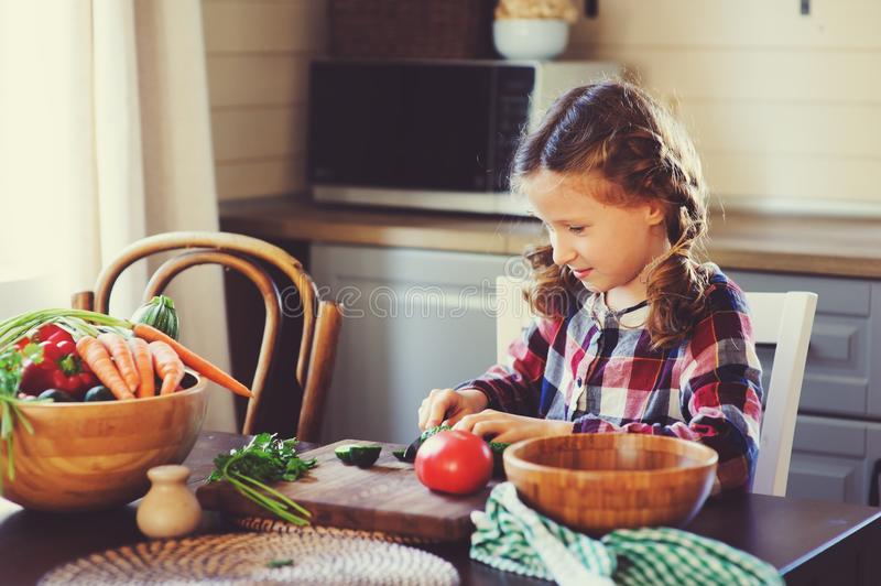 8 years old child girl help mom to cook vegetable salad at home. Healthy eating, little helper concept royalty free stock photos