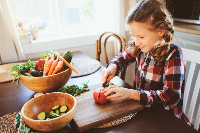 8 years old child girl help mom to cook vegetable salad at home. Healthy eating, little helper concept stock photo