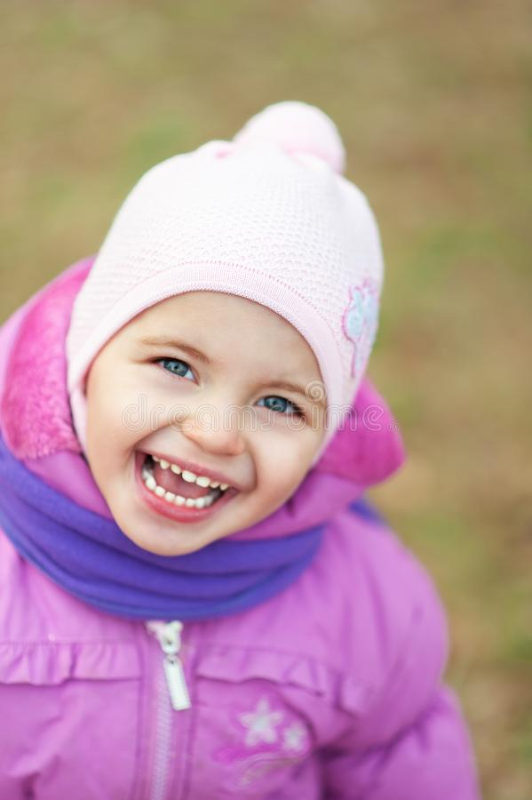 2 years old child in pink coat, pink hat and violet scarf with emotional expression on face outdoors. Autumn fall portrait of girl stock photos