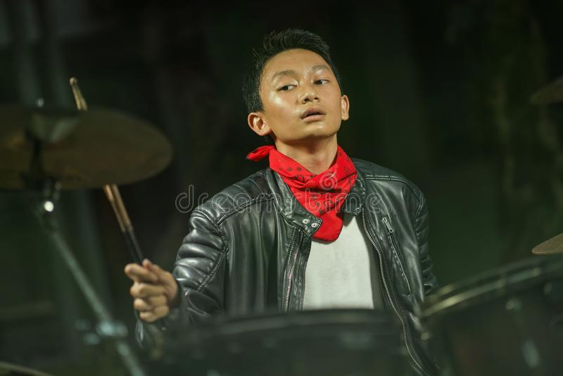 13 or 14 years old cool and talented Asian American mixed ethnicity boy playing drums in leather jacket and bandana  practicing stock photo
