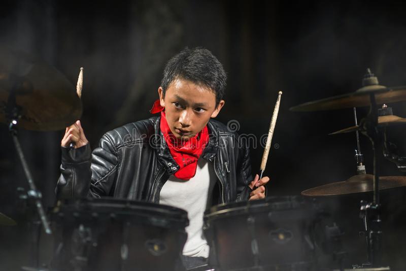13 or 14 years old cool and talented Asian American mixed ethnicity boy playing drums in leather jacket and bandana  practicing royalty free stock image