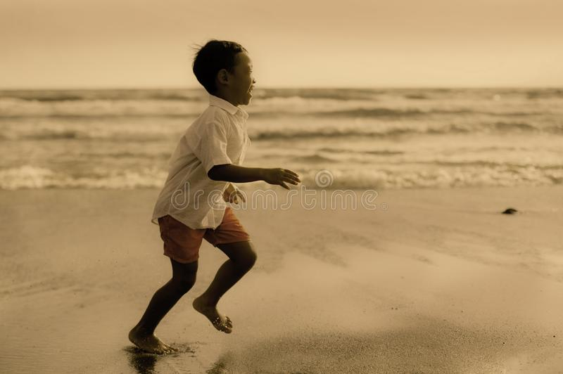 5 years old cute and happy child having fun on the beach playing free at the sea enjoying holidays running excited and cheerful in. Family travel vacation and stock photography