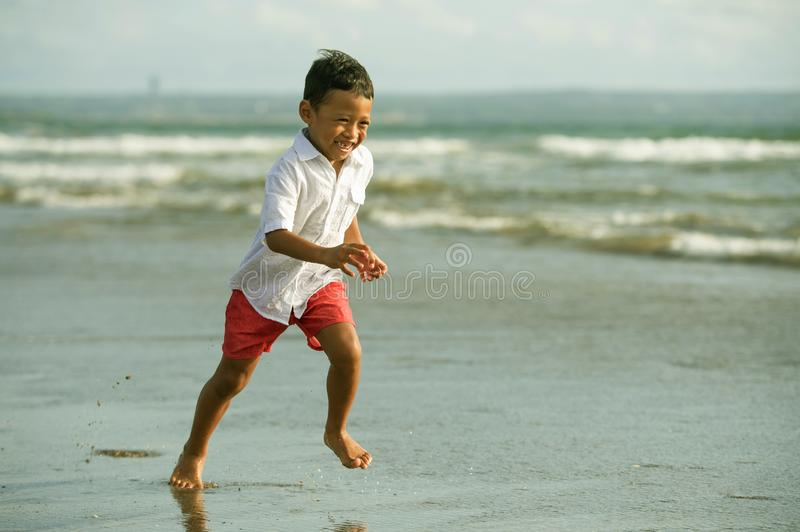 5 years old cute and happy child having fun on the beach playing free at the sea enjoying holidays running excited and cheerful in. Family travel vacation and royalty free stock images