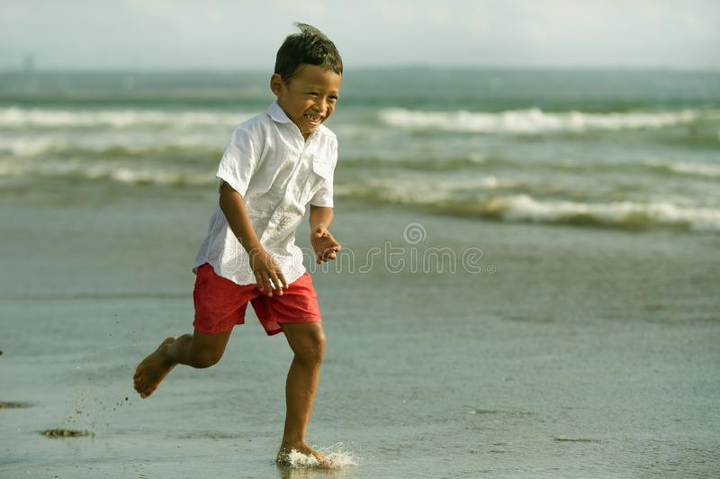 5 years old cute and happy child having fun on the beach playing free at the sea enjoying holidays running excited and cheerful in. Family travel vacation and royalty free stock image