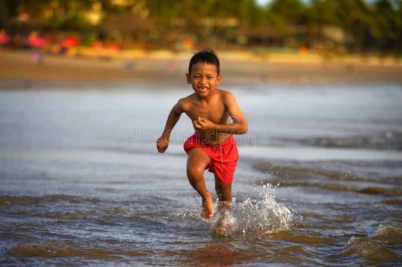 5 years old cute and happy child having fun on the beach playing free at the sea enjoying holidays running excited and cheerful in. Family travel vacation and stock photo