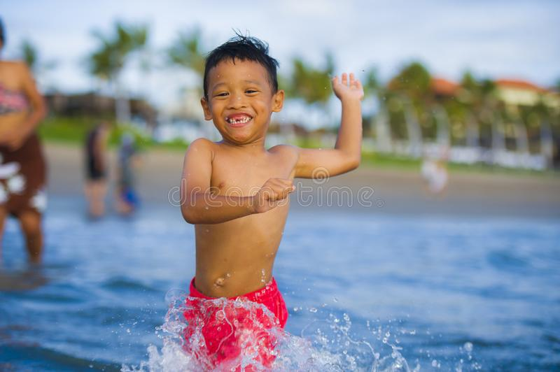 5 years old cute and happy child having fun on the beach playing free at the sea enjoying holidays running excited and cheerful in stock photography