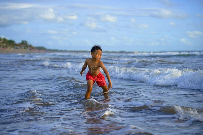 5 years old cute and happy child playing crazy free having fun on the beach splashing on water and sea waves enjoying holidays. Excited and cheerful in travel royalty free stock images