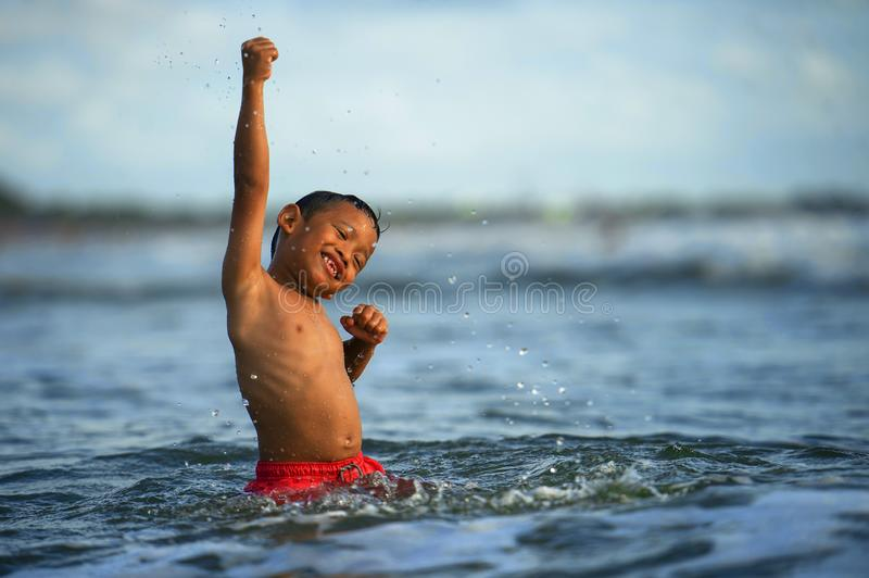 5 years old cute and happy child playing crazy free having fun on the beach splashing on water and sea waves enjoying holidays. Excited and cheerful in travel royalty free stock photo