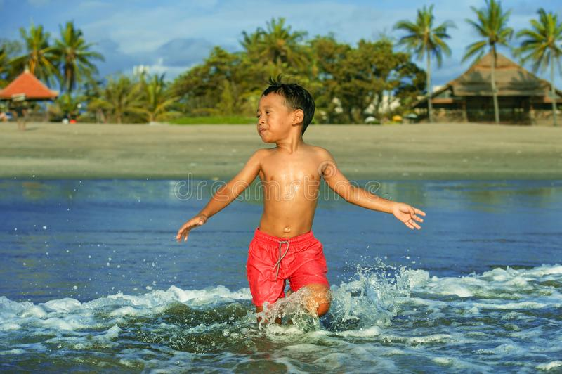 5 years old cute and happy child playing crazy free having fun on the beach splashing on water and sea waves enjoying holidays. Excited and cheerful in travel stock images