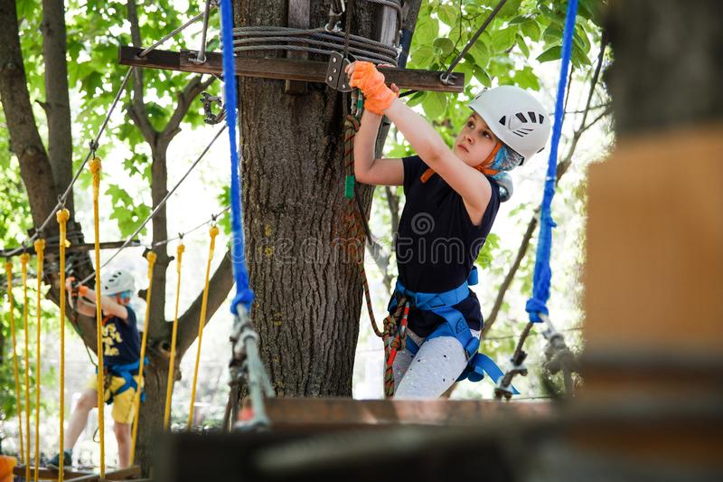 8 years old girl in forest adventure park. Child climb on high rope trail. Outdoor playground with rope way royalty free stock images